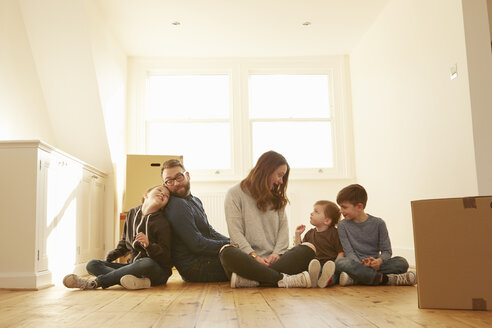 Mid adult couple and three children sitting on floor in new home - CUF10912