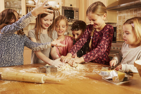 Boy and girls fooling around while baking at kitchen table - CUF10921