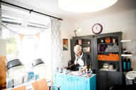 Woman at reception desk of quirky hair salon - CUF10968