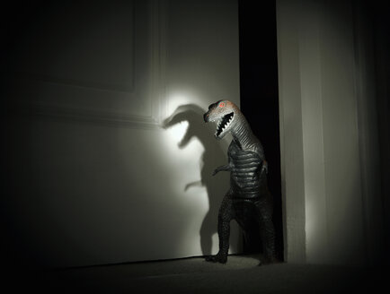 Toy dinosaur spotlit in darkened doorway - CUF11172