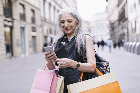 Stylish mature female shopper looking at smartphone on street, Florence, Italy - CUF11274