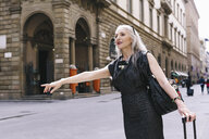 Mature woman with long grey hair with wheeled suitcase hailing a cab in Florence, Italy - CUF11277