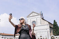 Stylish mature woman taking selfie in front of Santa Maria Novella church, Florence, Italy - CUF11280