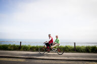 Quirky couple sightseeing on tandem bicycle, Bournemouth, England - CUF11292