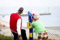 Quirky couple using tower viewer, Bournemouth, England - CUF11298