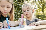 Sisters colouring out in garden - CUF11319