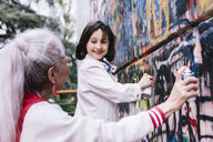 Mature woman and girl spray painting graffiti wall together - CUF11376