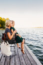 Mother and daughter sitting on pier by water - CUF11409