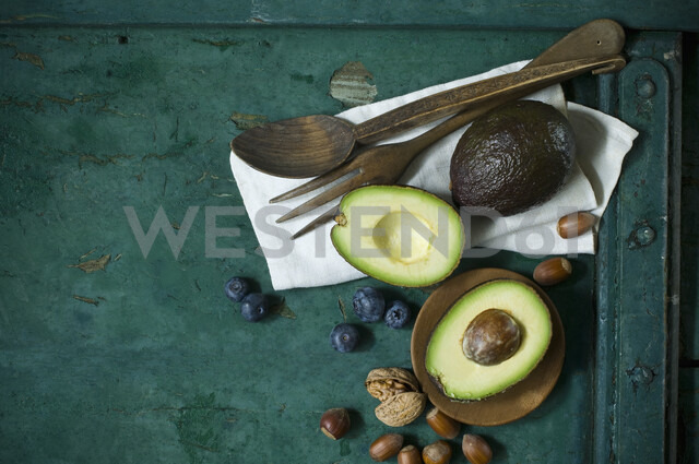 Cloth, salad cutlery, avocados, blueberries and nuts on green ground - ASF06186