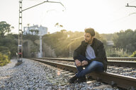Young man sitting on railroad track - AFVF00476