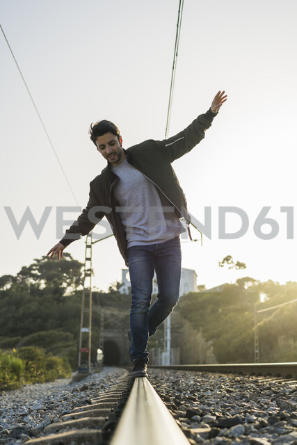 Young man standing on railroad track - AFVF00479