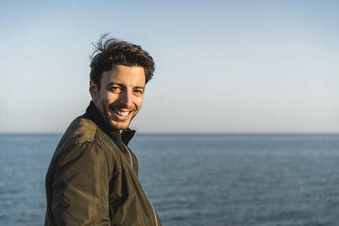 Portrait of smiling young man at the beach - AFVF00482