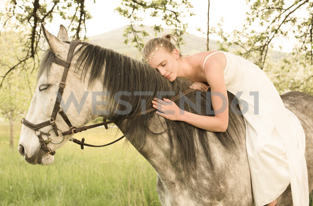 Beautiful young woman riding horse, wearing white summer dress - FCF01396
