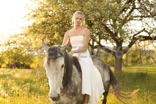 Beautiful young woman riding horse, wearing white summer dress - FCF01399
