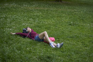 Young woman lying on a meadow listening music with headphones and cell phone - BEF00093