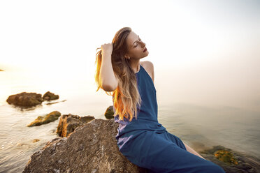 Young woman sitting on beach rock with hand in long hair, Odessa, Ukraine - CUF11476