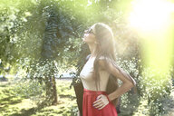 Young woman with long hair standing in sunlit foliage, Kotor, Montenegro - CUF11482