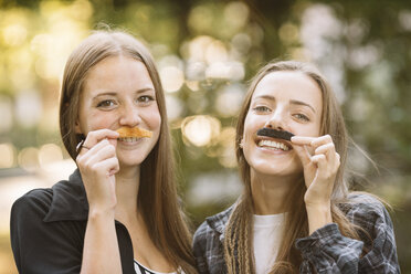 Portrait of two young female friends holding false moustache to their face in park - CUF11512