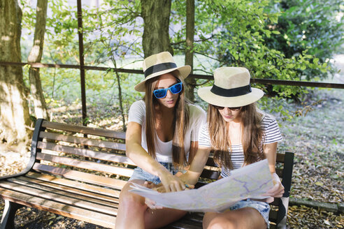Two young female friends sitting on bench looking at map in park - CUF11563