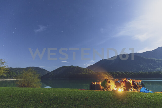 Germany, Bavaria, Sylvenstein Dam, Group of people at camp fire during night - MMAF00350