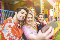 Group of friends at fairground, taking selfie, using smartphone - CUF11754