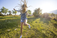 Fun young woman with long plaited blond hair jumping for joy in field, Majorca, Spain - CUF11811