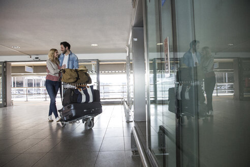 Happy young couple with luggage trolley airport terminal - CUF11826