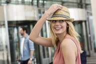 Young woman wearing trilby outside airport terminal - CUF11829