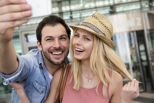 Young couple taking smartphone selfie outside airport terminal - CUF11835