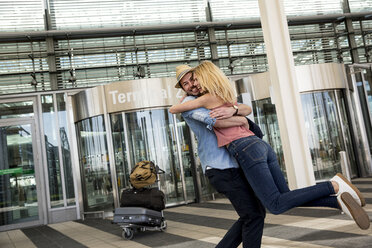 Young couple hugging outside airport terminal - CUF11838