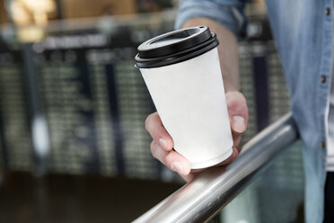 Hand of young man holding coffee in airport departure lounge - CUF11844