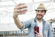 Young man holding passport taking selfie in airport departure lounge - CUF11847
