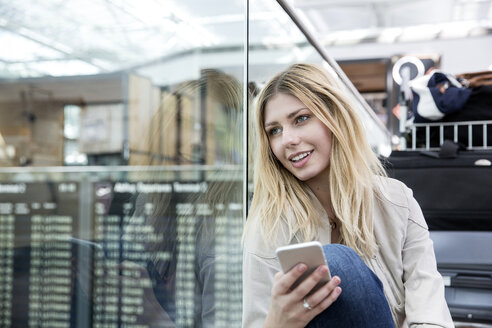Young woman with smartphone gazing in airport terminal - CUF11850