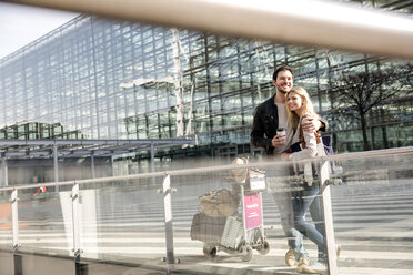 Young couple with coffee and baggage trolley outside airport - CUF11853