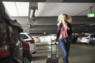 Young woman running with wheeled suitcase in airport carpark - CUF11856