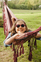 Portrait of smiling girl wearing sunglasses lying in hammock - ANHF00045
