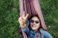 Smiling girl wearing sunglasses lying in hammock showing victory sign - ANHF00048