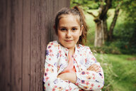 Portrait of smiling girl leaning against wooden wall - ANHF00054