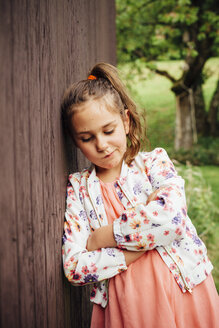 Portrait of sad girl leaning against wooden wall - ANHF00057