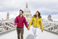 UK, London, young couple walking hand in hand on bridge in front of St Pauls Cathedral - WPEF00278