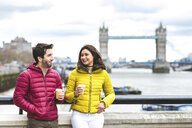 UK, London, couple with coffee to go standing on bridge over the Thames - WPEF00284