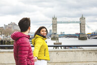 UK, London, young couple walking hand in hand on bridge over the Thames - WPEF00287