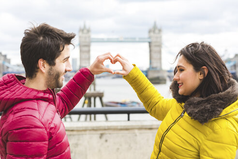 UK, London, young couple standing on bridge over the Thames forming heart with their hands - WPEF00290