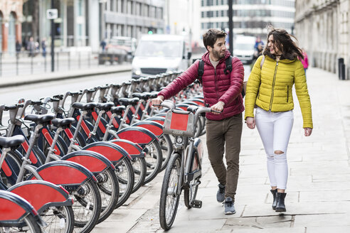 UK, London, young couple with bicycle from bike share stand walking in city - WPEF00293