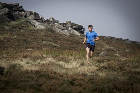 Male runner running down from Stanage Edge, Peak District, Derbyshire, UK - CUF11862