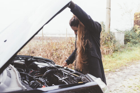 Woman looking at car engine on roadside - CUF11910