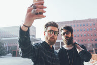 Two cool young male hipsters taking smartphone selfie in city - CUF12036