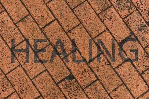 Word 'Healing' stenciled on red pavement - AFVF00492