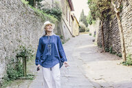 Stylish mature woman strolling on cobbled street, Fiesole, Tuscany, Italy - CUF12074