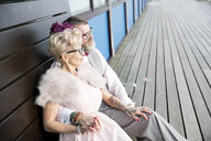 1950's vintage style couple sitting on pier bench - CUF12095